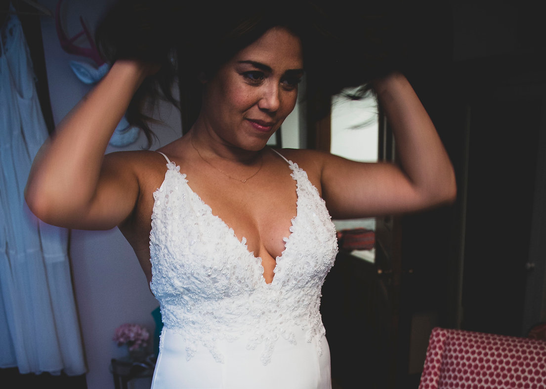 Bride getting ready for her wedding - Lifting up her hair getting zipped up . Backyard wedding - Wedding photography