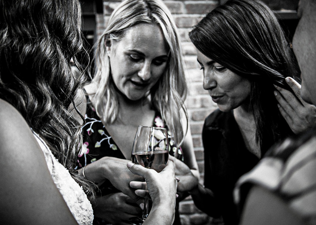 Woman showing off her wedding ring to girlfriends at party  - Wedding photography - Black and white photography