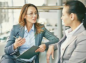 Duas mulheres executivas conversando. Uma, com uma prancheta em mãos, é a coach e a outra, ouvindo atentamente, é a coachee