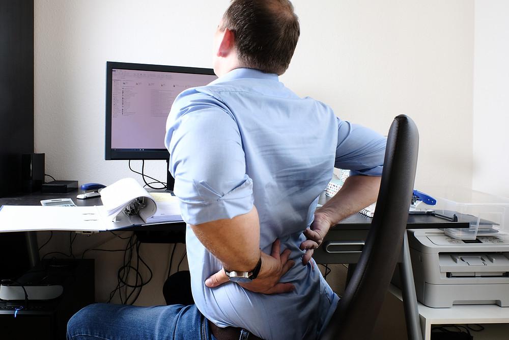 Rückenschmerzen durch zu vieles Sitzen im Büro