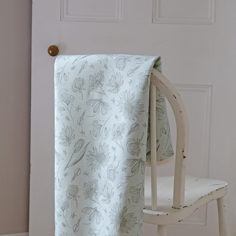 Cutting Garden fabric on the back of a chair