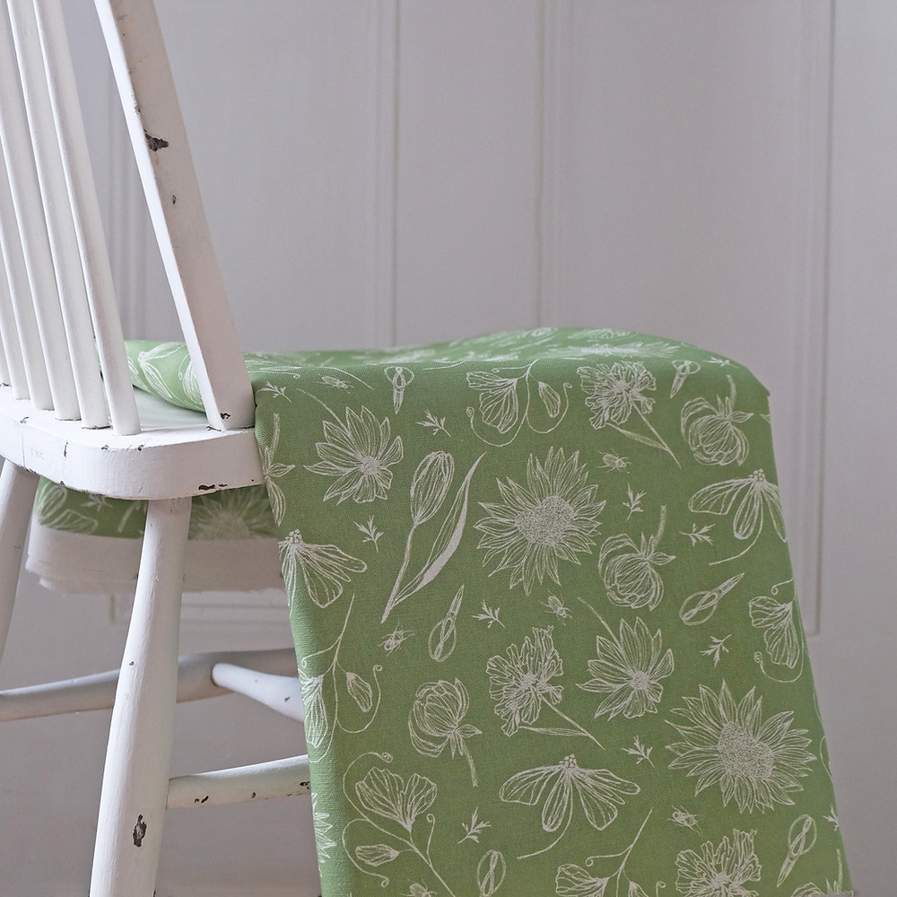 Green linen floral fabric hanging over a rustic chair