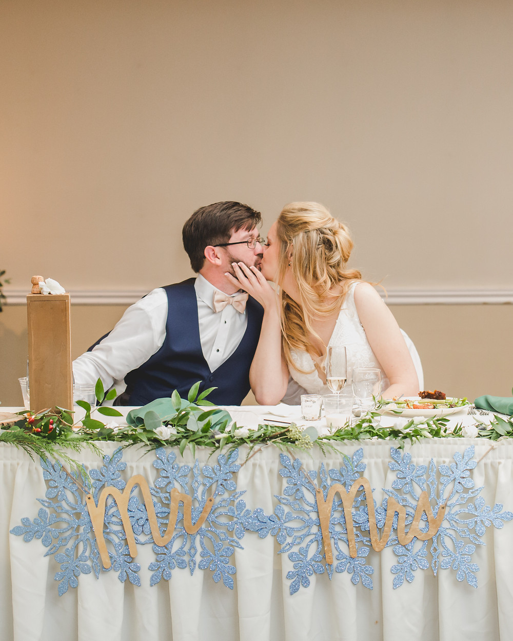 Bride and groom kiss at head table, winter wedding, Composed and Exposed Photography, Riverview Banquets Batavia IL,