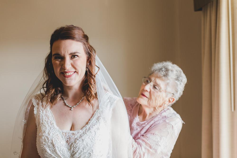 Grandmother helping bride with wedding dress