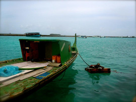 Maldives, man cleaning his boat.jpg