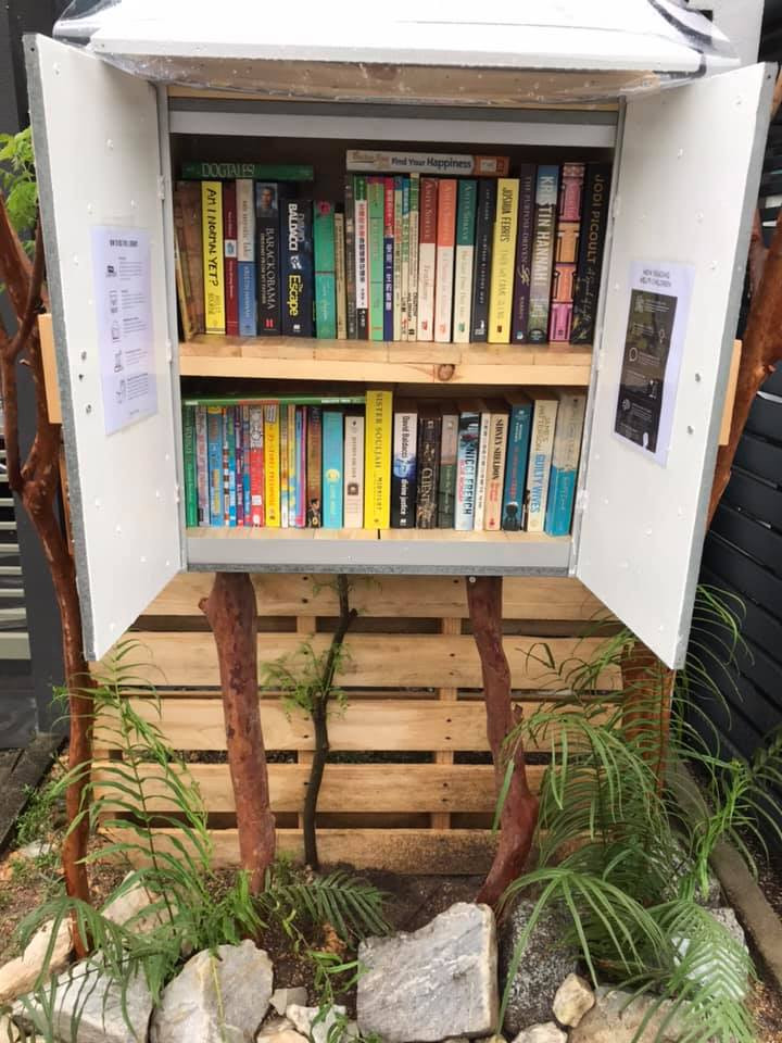 A makeshift outdoor shelf with books outside a home.