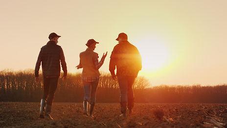 Three-farmers-go-ahead-on-a-plowed-field