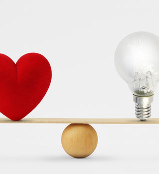 Heart and light bulb on scale - Concept