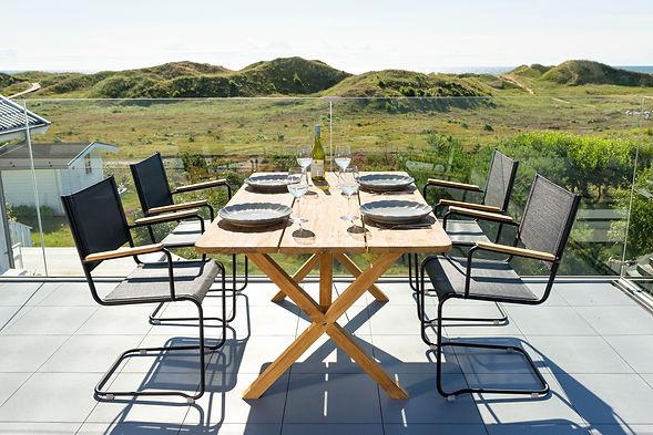 inout form Summer 52 vit fåtölj i svart och ett rektangulärt teakbord