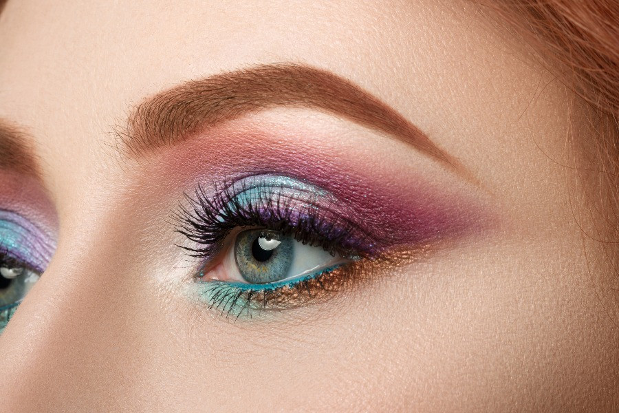 bright blue and pink eye makeup on woman