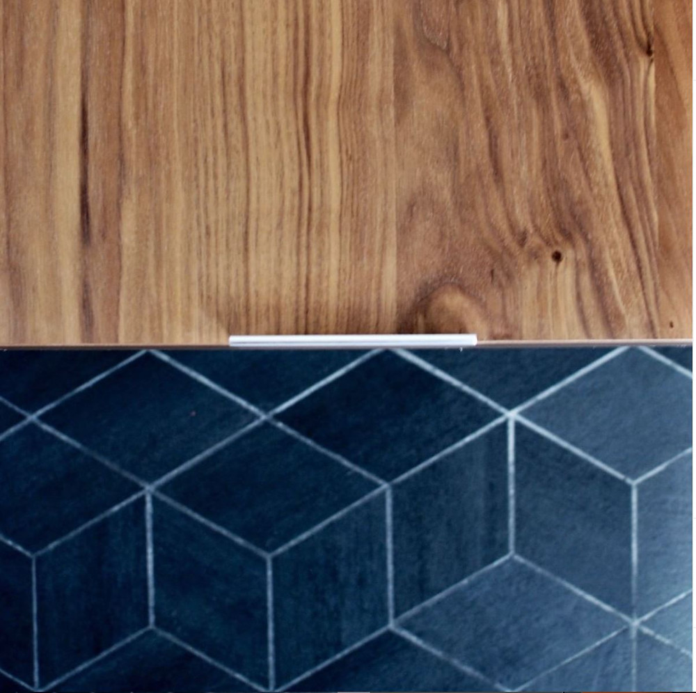 A pleasant marriage of natural walnut and black geometric tile with a sleek brushed finger pull to keep it streamlined.