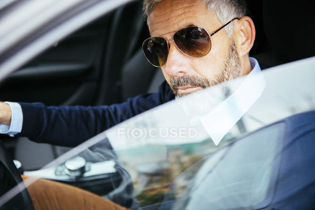 focused_180120660-Man-sunglasses-driving-car.jpg