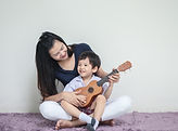 Asian mother teach her son to play ukulele on carpet with copy space_edited.jpg