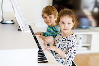 Two little kids girl and boy playing pia