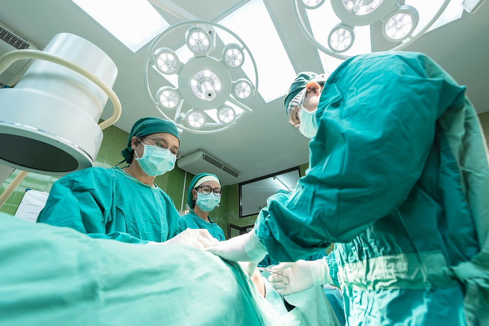 Leikkaussalissa potilas ja henkilökuntaa