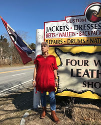 Woman in red deerskin handmade shirt in front of Four Winds Leather Shop sign