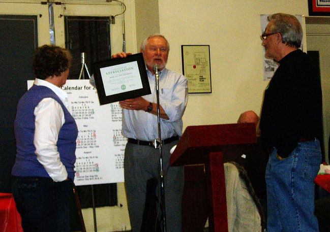 Henry is making a presentation to Ron and Pat Cottrell recognizing their support over the last few years with the sale of Chocolates.  Photo by Jan Burgess