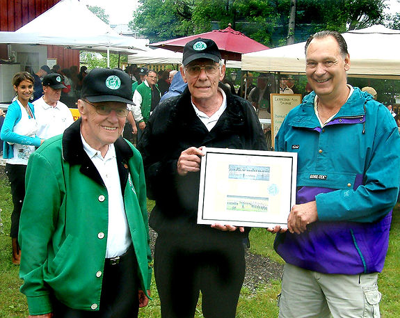 Presentation of a plaque created by Phil Hennings. What's on it? Some words plus a a York Lions crest and photo (Bob played in York) as well as an Optimists crest together with a photo of the alumni corps. photo by Frans Rood