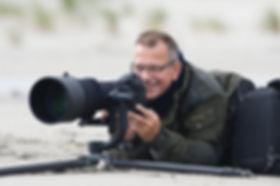 Henk Laverma ligt op het strand van Terschelling om drieteenstrandlopers te fotograferen.