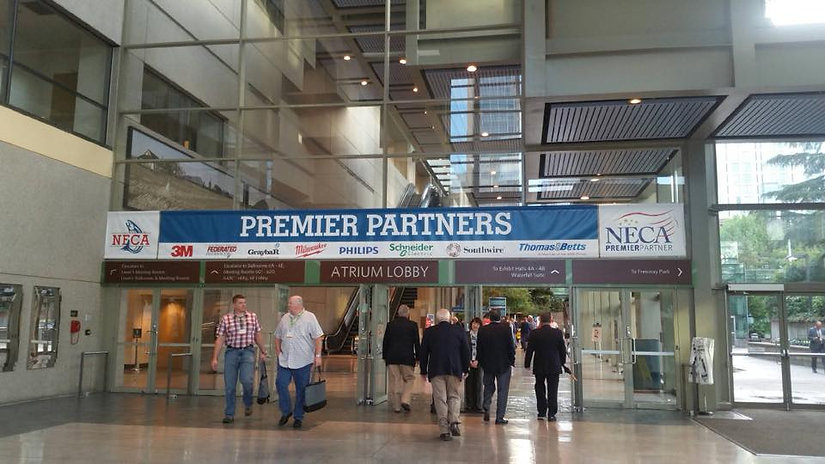 Walk way in a convention center with people entering and exiting the doorway.