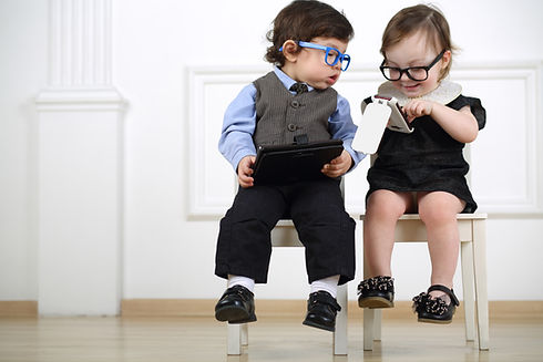 Two little kids in glasses sitting on wh