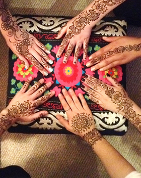 Henna on hands on top of a beautiful stool.
