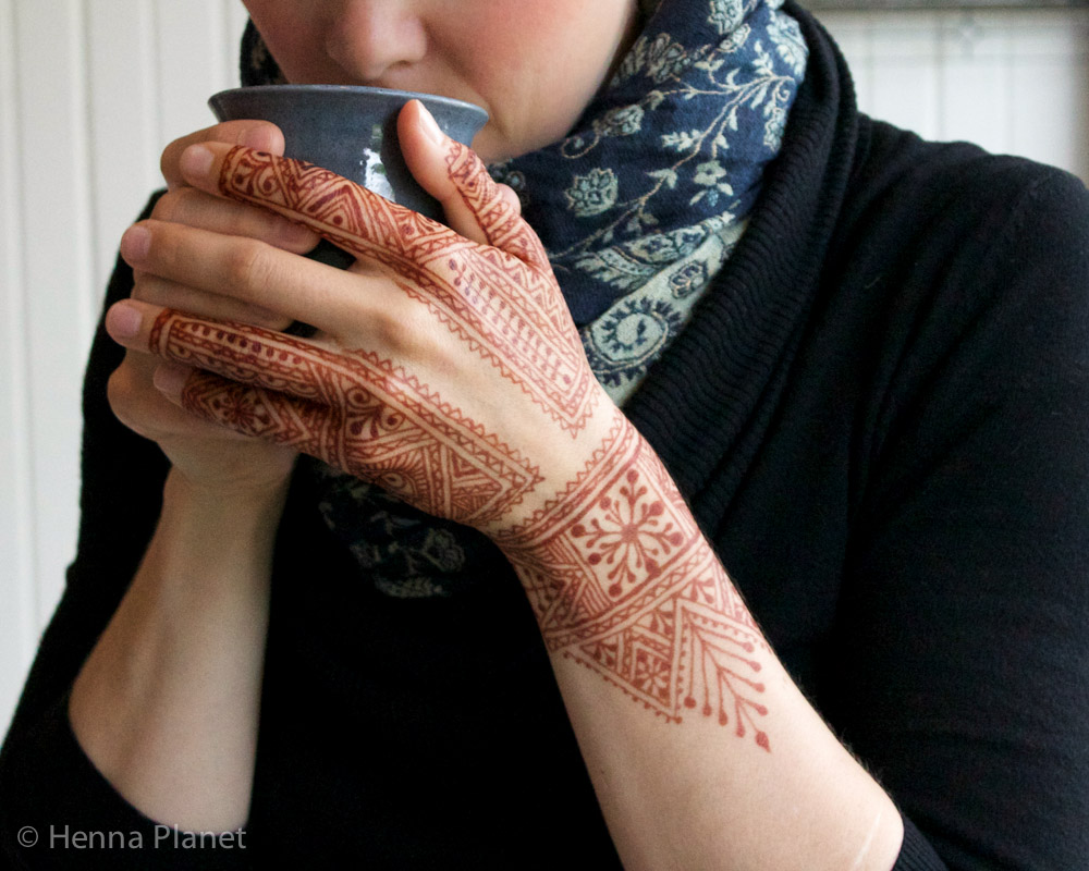 Moroccan henna on a hand with mug.
