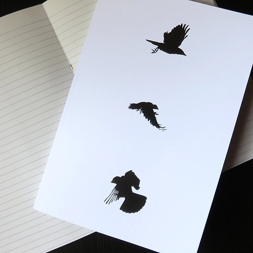 three flying crow birds in black on a white notebook