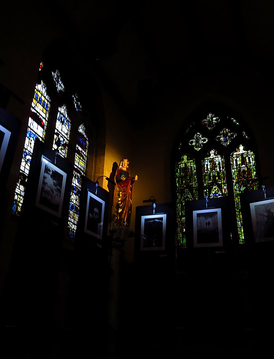 A dark close-up view of the artwork setup at All-Saints. Dim light comes in through the stained glass windows. An orange spotlight lights up a statue of the virgin Mary, and each piece of artwork is illuminated only by a dim, white light above them. The bottom of the image is lost in shadow.