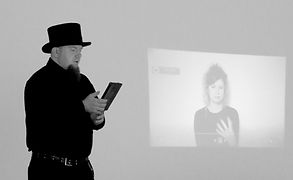 Sean Walter in a top hat reads a story in front of a projection of a woman doing a British Sign Language interpretation of the story.