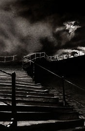 Charcoal illustration of the base of the 199 steps in Whitby, UK. The moon is obscured by clouds and The Barghest, a large wolf-like creature, is climbing the steps.