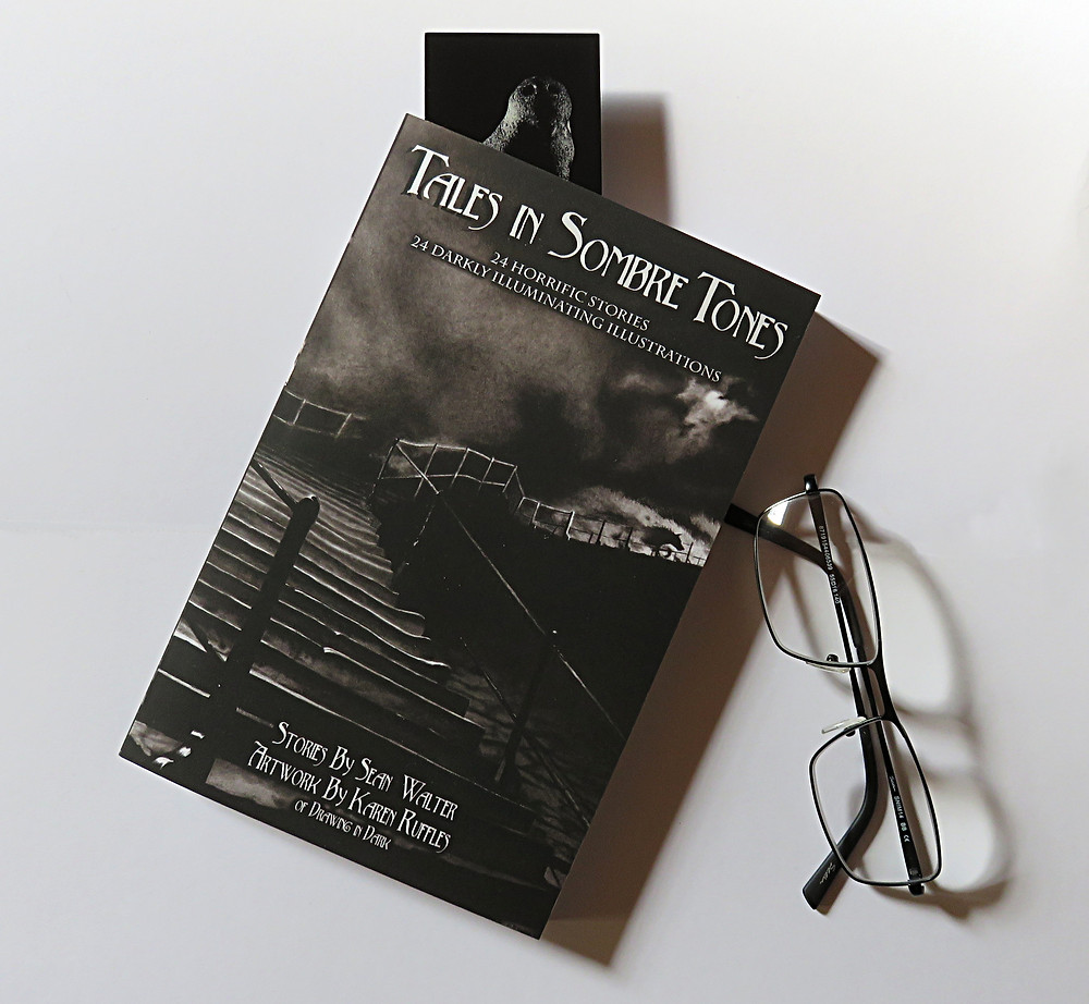 paperback copy of Tales in Sombre Tones next to reading glasses