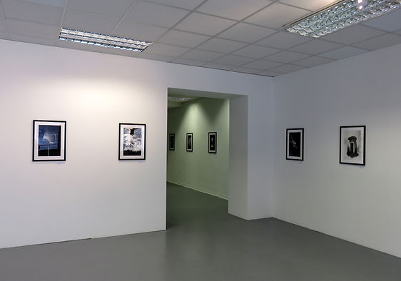 A sterile-looking room: White walls, white ceiling, and a stone-grey floor. The only thing that stands out is the dark, charcoal artwork that perfectly lines the walls.