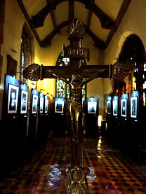 A bronze crucifix in the forground. In the background, a series of illustrations hung on black cloth stands.