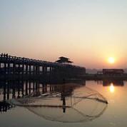 Casting nets under the U Bein bridge at sunset