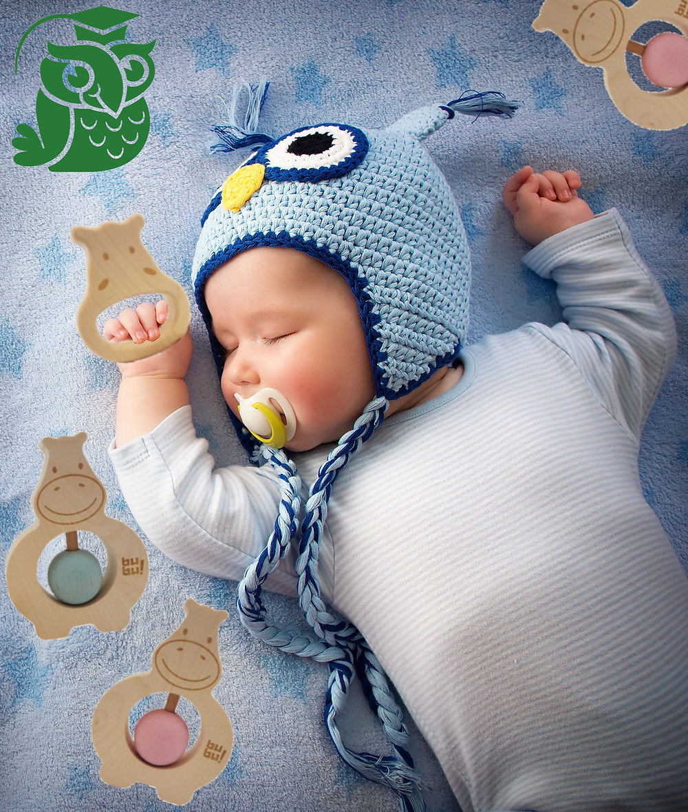 Sleeping baby with owl knitted hat and holding a wooden teether.