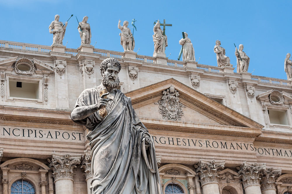 the statue of St. Peter in front of the facade of the basilica