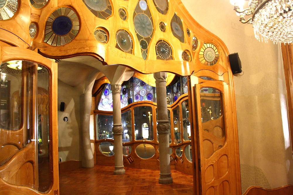 the entrance hall of the Casa Battlo with curving doors and windows and a massive crystal chandelier