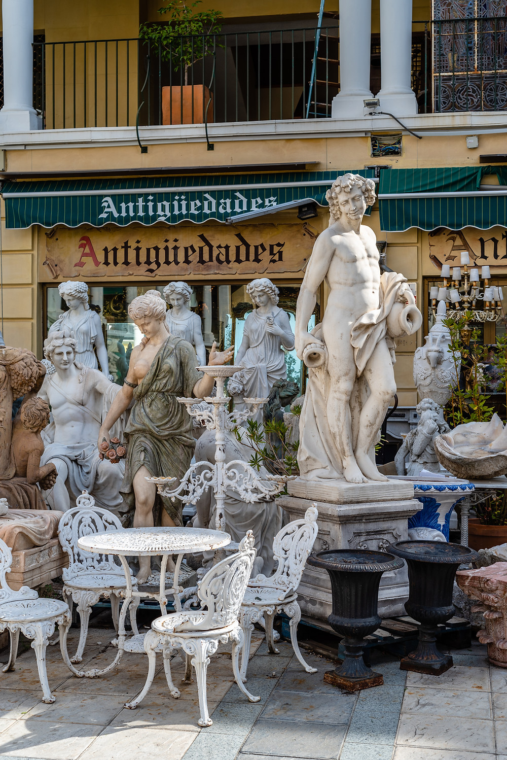 sculptures and garden furniture in an antique store in El Rastro