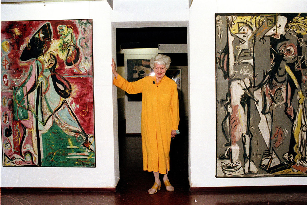 Peggy Guggenheim poses with her early Pollocks