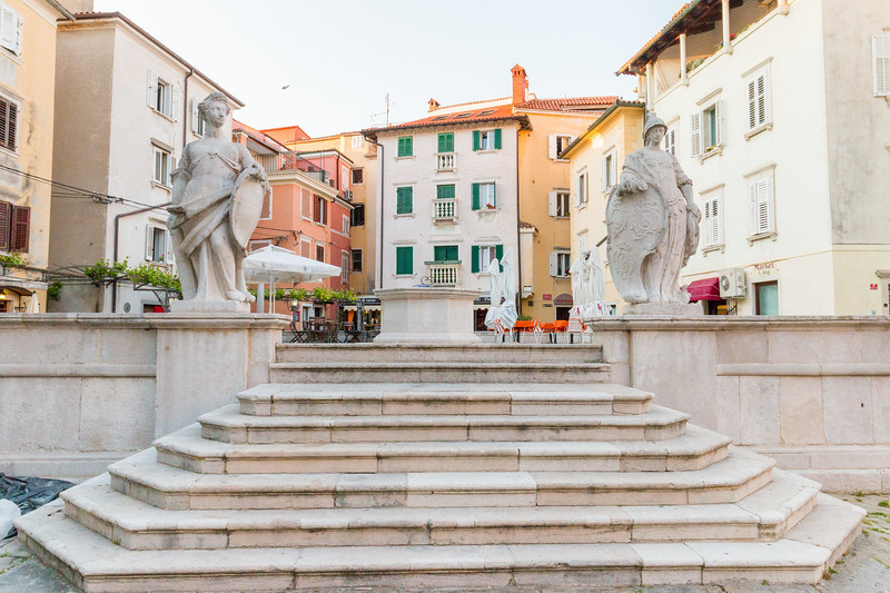 the First of May Square in Piran, with a stone cistern flanked by the statues representing Strength and Vigilance
