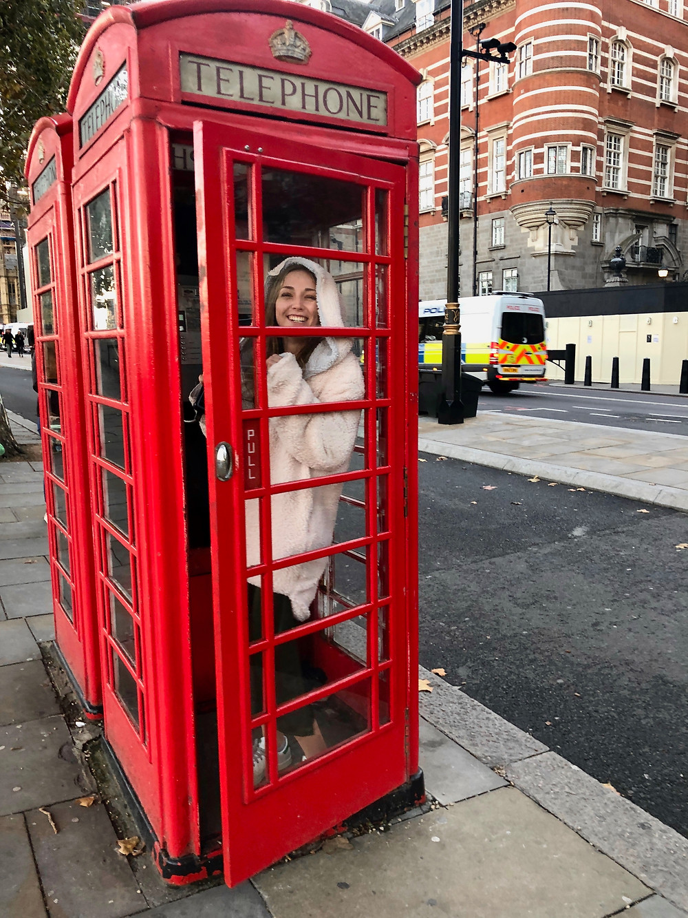 my daughter, enjoying the photo ops in a classic red London phone booth