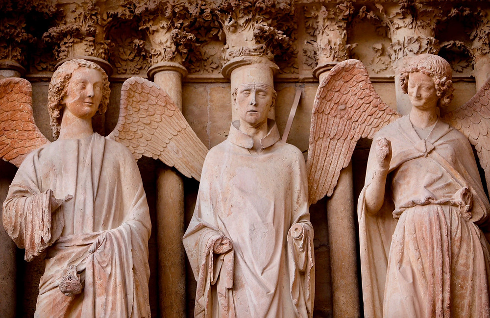 "statues on the facade of Reims Cathedral, with the ""Smiling Angel"" on the right"
