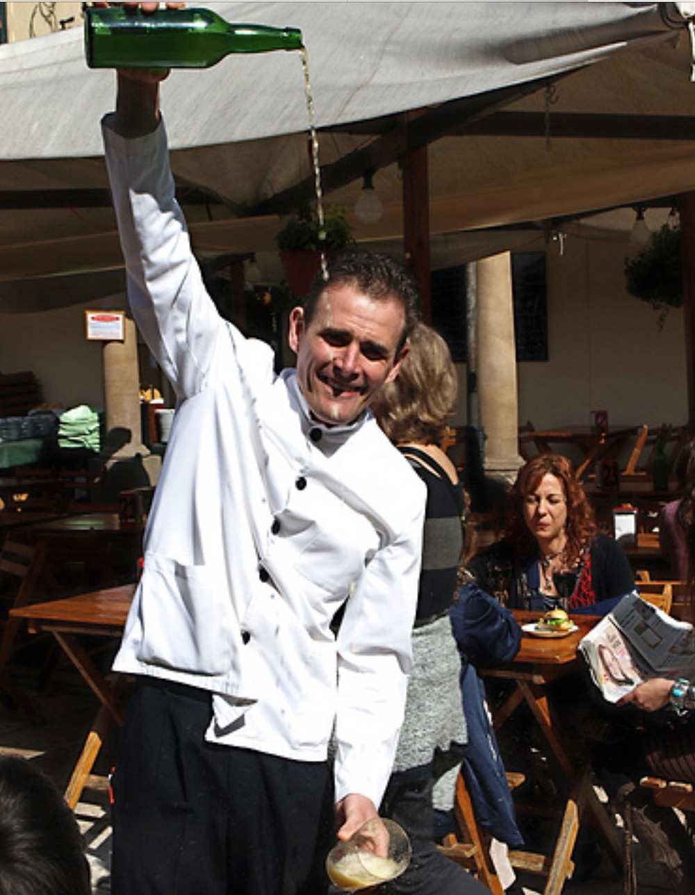 a waiter pouring cider, performance art style,  in Oviedo Spain, the capital of Asturias