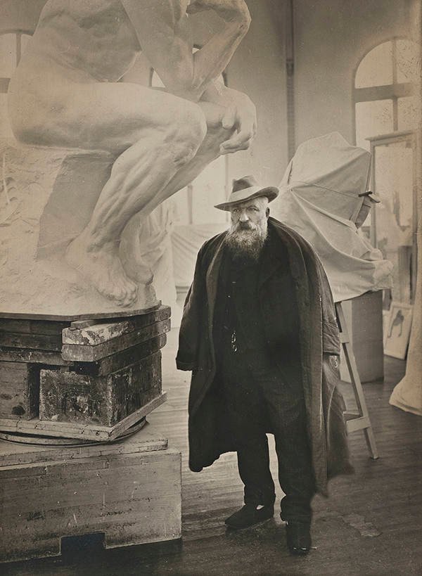 Rodin in his studio next to a plaster model of The Thinker
