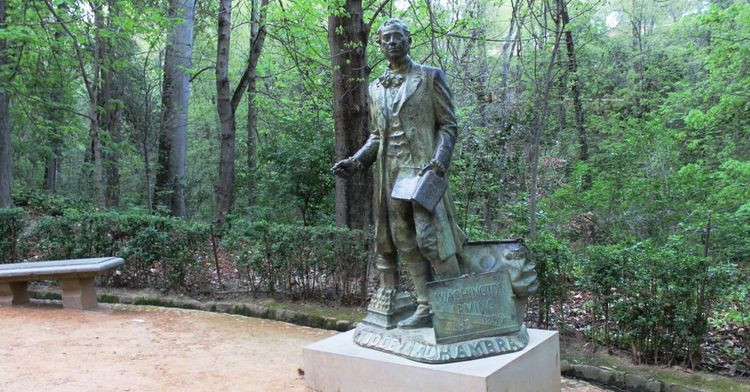 "a statue of Washington Irving in a park outside the Alhambra with the inscription ""Son of the Alhambra"""