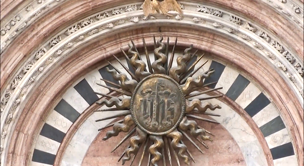 he sunburst in the central portal of the facade of Siena Cathedral
