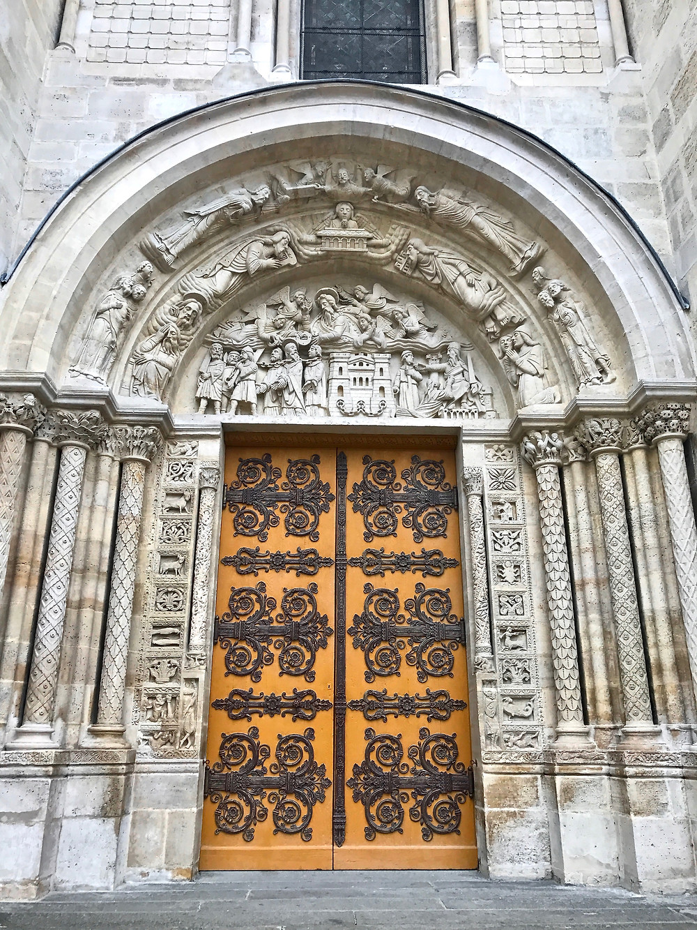 the central entry door to the Basilica de Saint-Denis with ornate wrought iron strap hinges