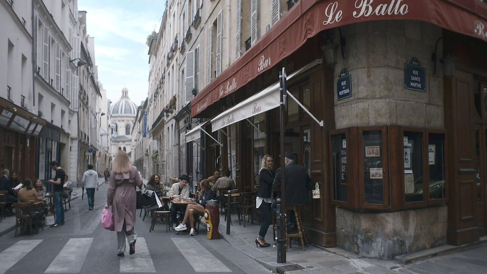 Villanelle walking down Rue Mazarine in Paris -- a street filled with shops, art galleries, and tony restaurants