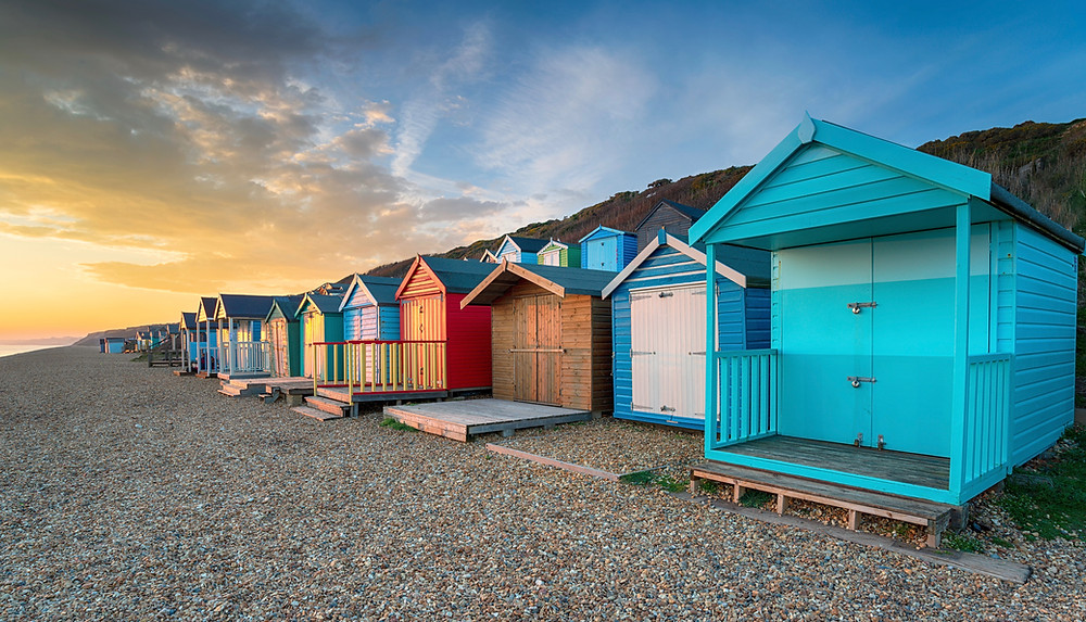 sunset over a row of brightly coloured beach huts at Milford on Sea in NH